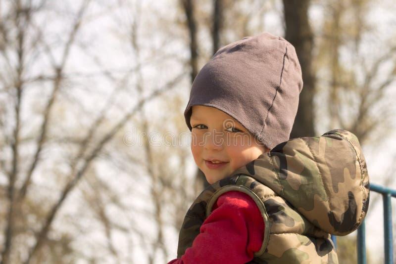 一个男孩在秋天森林,被弄脏的背景,拷贝空间里 库存图片