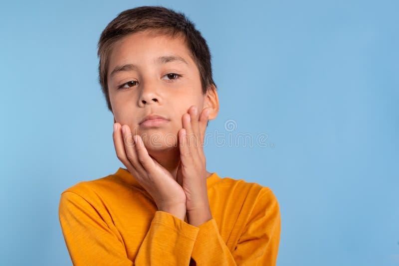 一个男孩的演播室情感射击一件黄色衬衣的在与copyspace的蓝色背景 他接触他的面颊棕榈和 免版税库存图片