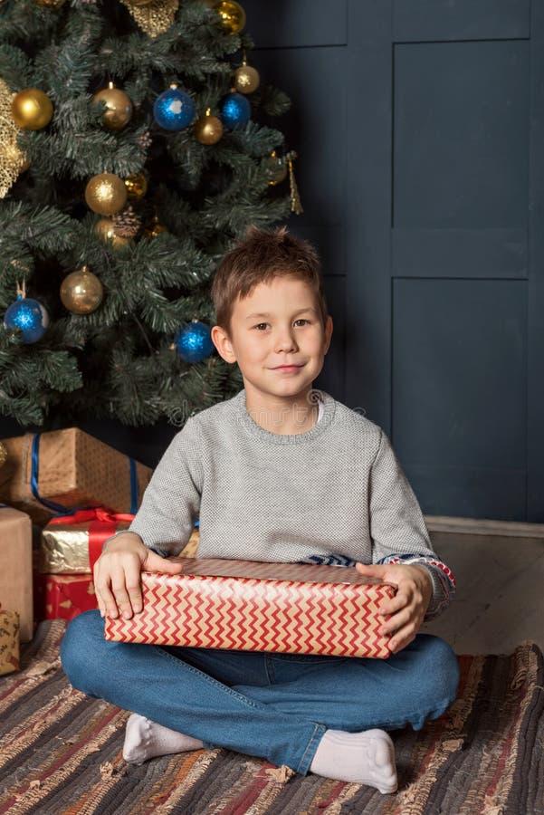 一个男孩的画象有一个礼物盒的在他的在新年圣诞树附近的手上 库存照片