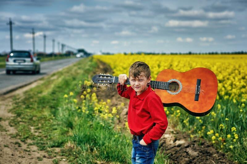 一个男孩的画象有一把声学吉他的在一个黄色领域 免版税库存照片