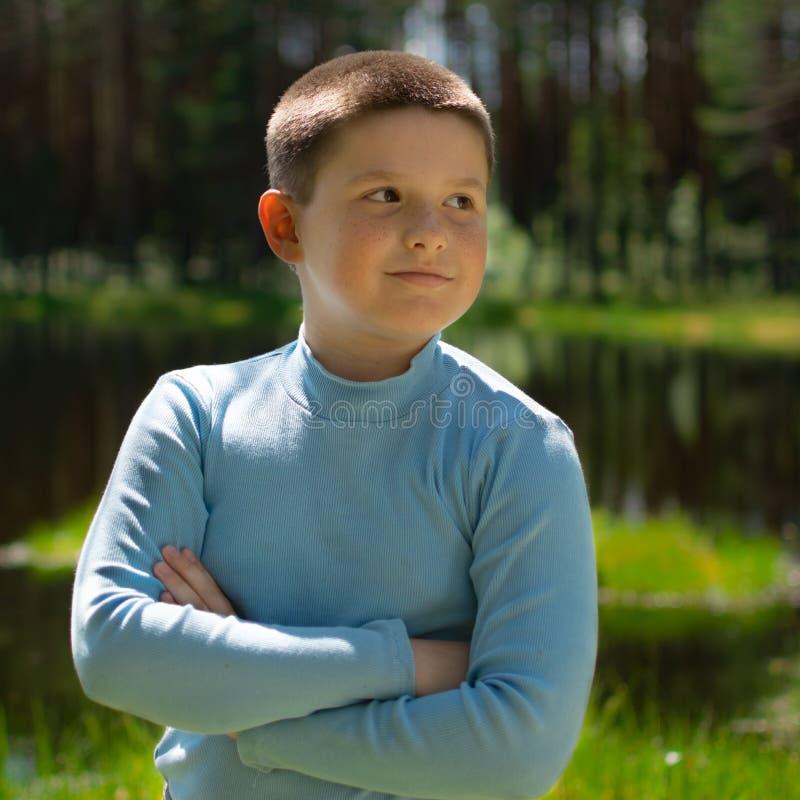 一个男孩的画象森林湖的背景的 免版税库存图片