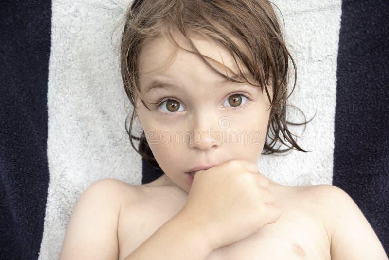 一个男孩6的画象有棕色头发和棕色眼睛的,与他的在嘴和大棕色眼睛的拇指他凝视摄影师 免版税库存照片