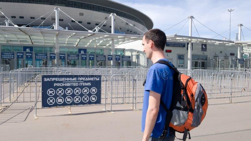 一个男性游人在出席一足球赛前审查与被禁止的项目的一个标志在圣彼德堡  免版税库存图片