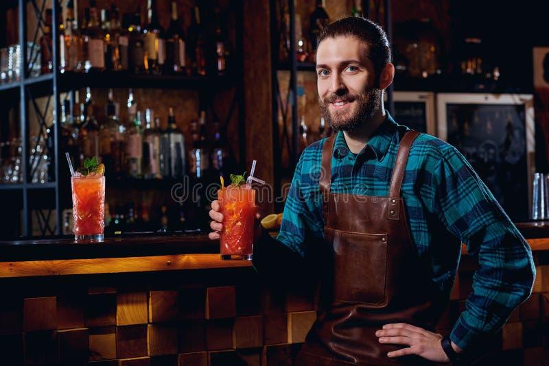 一个男服务员行家的画象有胡子微笑的坐的在酒吧 免版税图库摄影