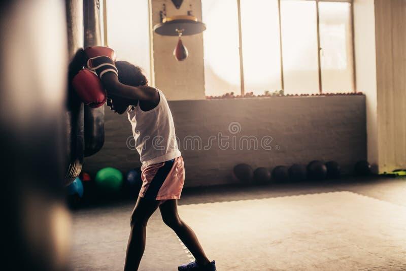 一个疲乏的拳击孩子的侧视图在拳击健身房的 库存照片
