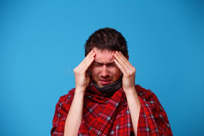一个病的人,包裹在毯子,拿着他的头 病症、头疼和偏头痛的概念 免版税库存图片