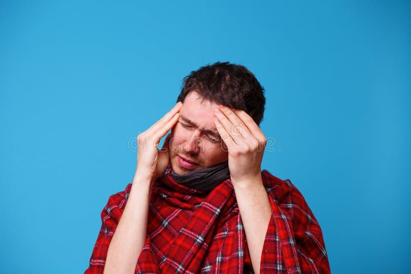 一个病的人,包裹在毯子,拿着他的头 病症、头疼和偏头痛的概念 库存图片
