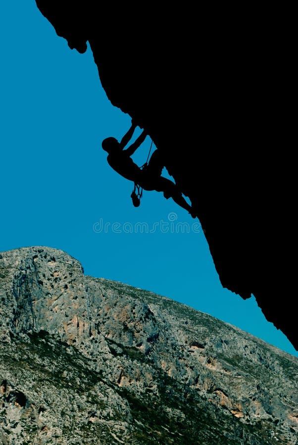 一个登山人的剪影一个伸出的岩石的反对backd 库存图片