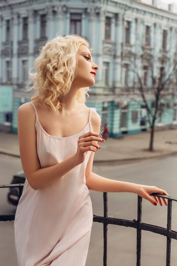 一个白肤金发的女孩在阳台摆在 免版税库存图片