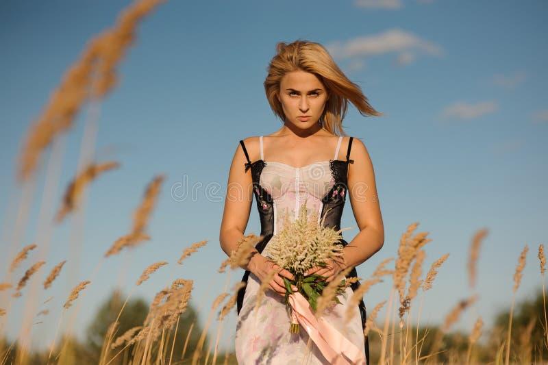 一个白肤金发的女孩的画象女用贴身内衣裤的在领域 免版税库存照片