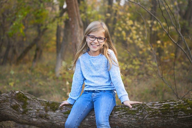 一个白肤金发的女孩的画象戴户外眼镜的在秋天公园背景的公园 免版税图库摄影