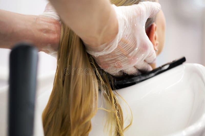 一个白肤金发的女孩的美发师洗涤的头发 免版税图库摄影