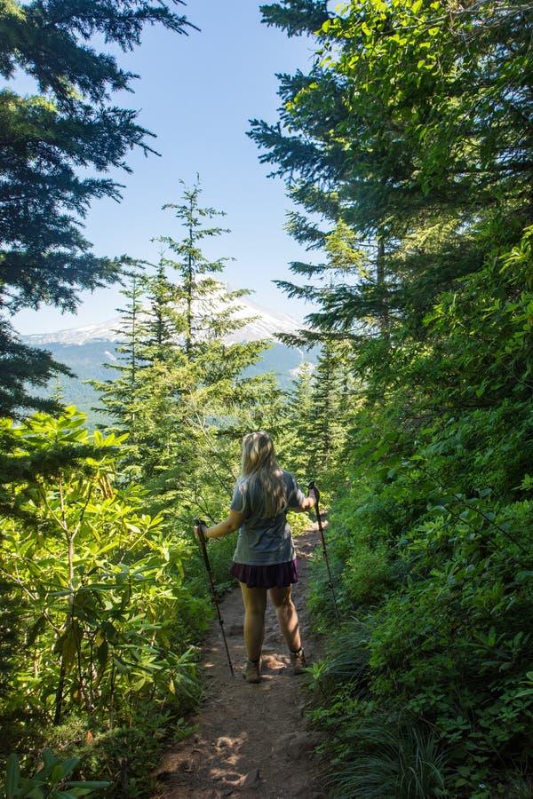 一个白肤金发的女性远足者通过森林做她的方式在Mirror湖足迹在胡德山国家森林里 免版税库存图片