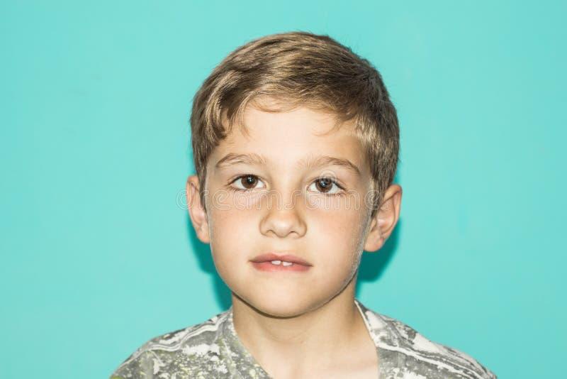 一个白肤金发的孩子的画象蓝色背景的 库存照片