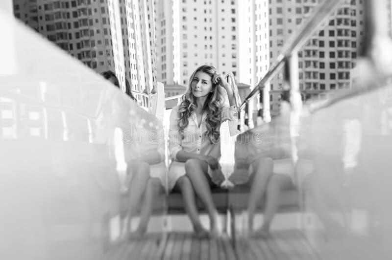 一个白肤金发的少妇的黑白照片小船的在迪拜 库存图片