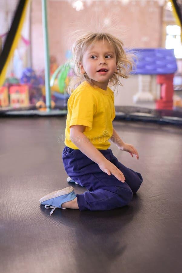 一个白肤金发的男孩的画象一件黄色T恤杉的 儿童微笑和戏剧在儿童的游戏室 孩子在跳 库存图片