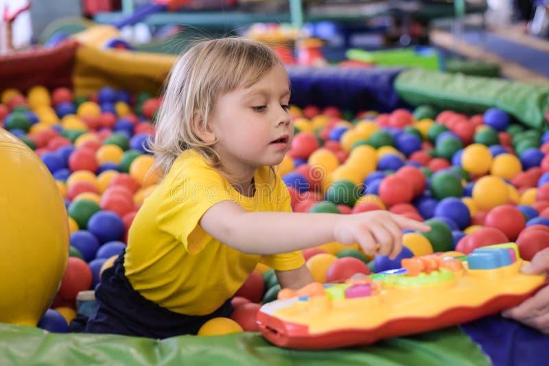 一个白肤金发的男孩的画象一件黄色T恤杉的 儿童微笑和戏剧在儿童的游戏室 球水池 图库摄影