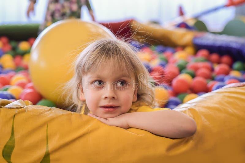 一个白肤金发的男孩的画象一件黄色T恤杉的 儿童微笑和戏剧在儿童的游戏室 球水池 免版税库存图片