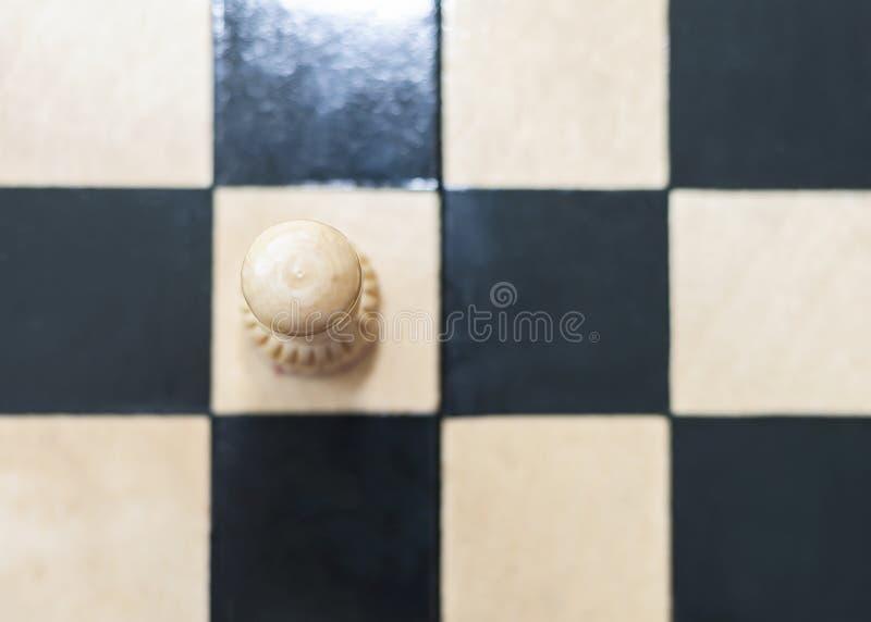 一个白色典当棋子在棋枰、隔离、寂寞或者个性概念单独站立 库存照片