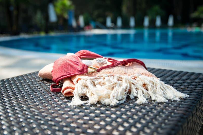 一个白色和橙色土耳其厚绒毛巾、比基尼乳罩和白色贝壳在藤条懒人与蓝色一个游泳池作为背景 免版税图库摄影