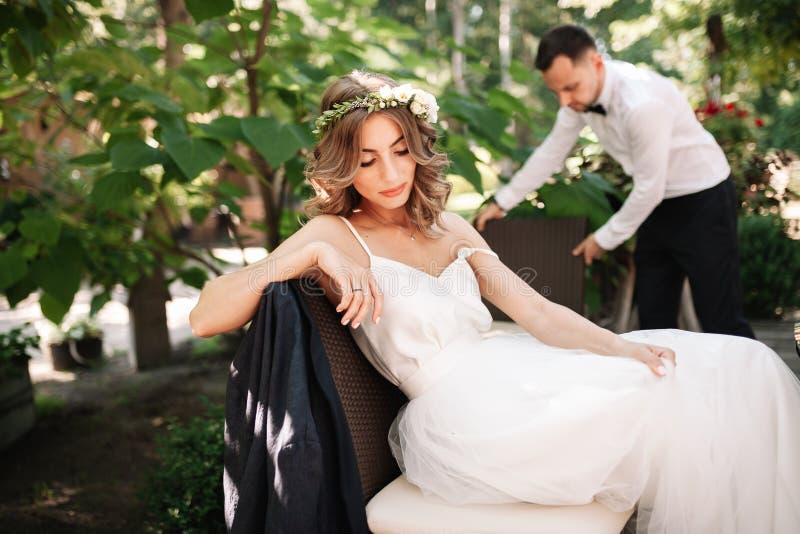 一个白色婚纱和花圈的一个美丽的新娘坐椅子在新郎旁边,休息和为幸福家庭做准备 免版税库存图片