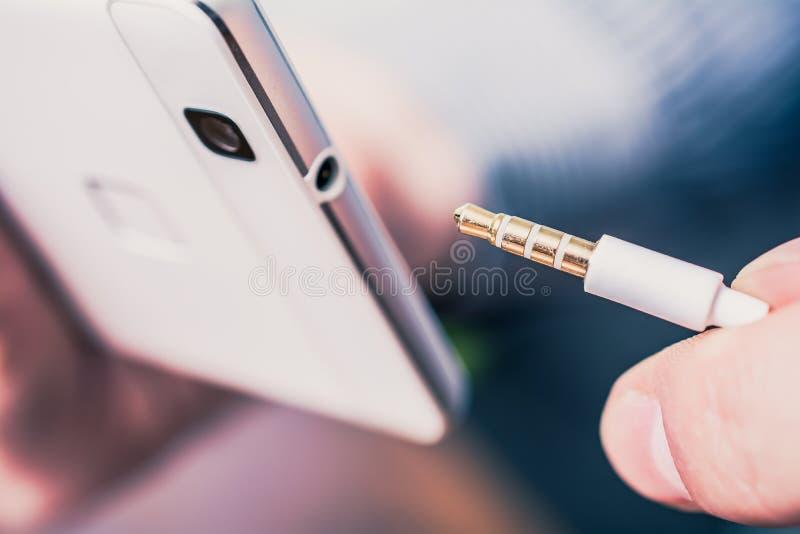 一个白色手机的耳机杰克在耳机缆绳旁边的 库存照片