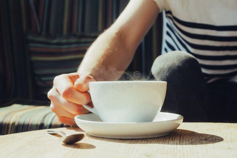 一个白色杯子无奶咖啡和人怎么得到它 库存照片