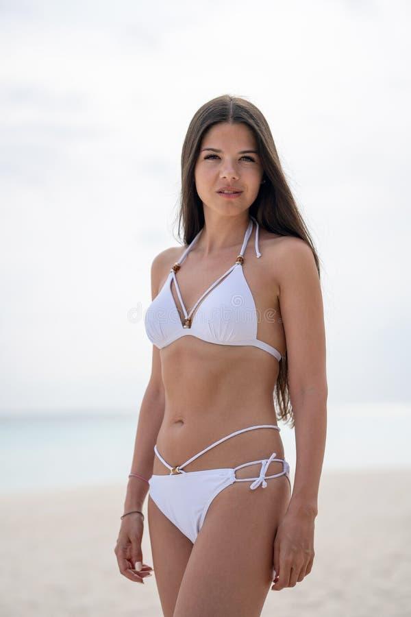 一个白色游泳衣身分的一少女在海滩 在背景中是绿松石水 免版税库存图片