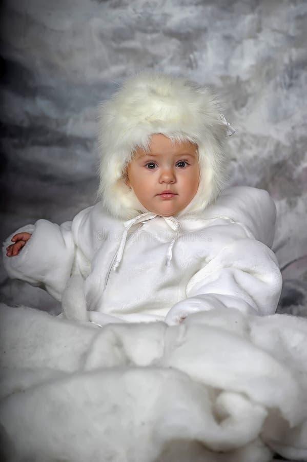 一个白色皮大衣和帽子的小女孩 库存照片