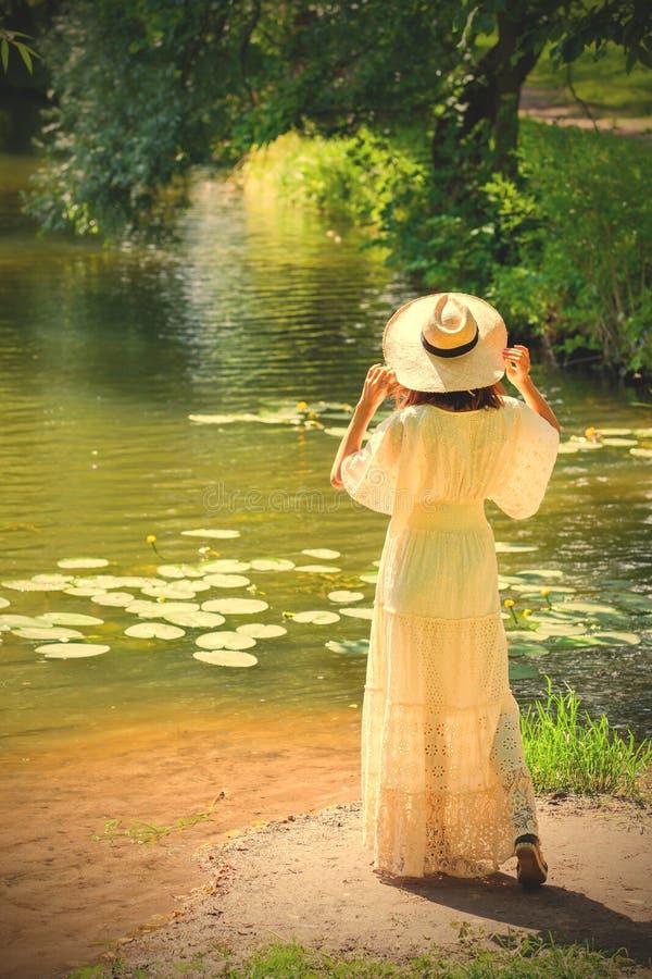 一个白色礼服和帽子的女孩在一个池塘的岸有水的 库存图片