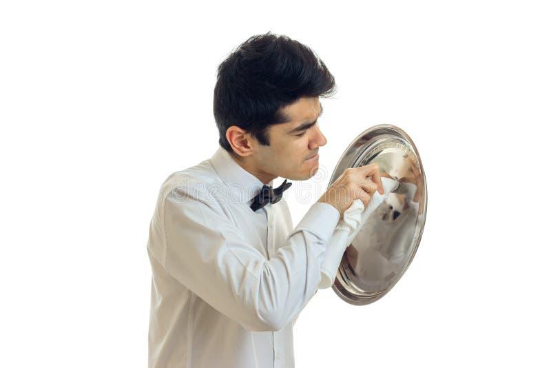 一个白色衬衣边毛巾盘子的年轻英俊的侍者炊具的 免版税图库摄影