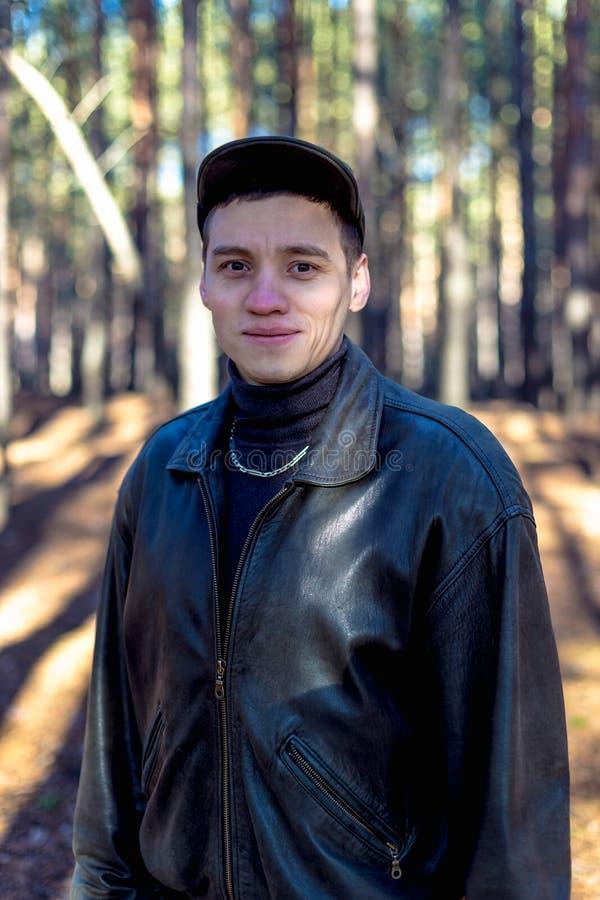 一个皮夹克和盖帽的一个人在一条路在杉木森林里 免版税库存图片