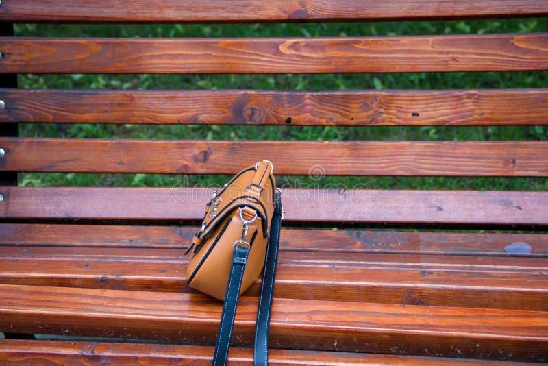 一个皮革时兴的夫人` s袋子的特写镜头,做在棕色颜色 她在一条老长凳站立在夏天公园 库存图片