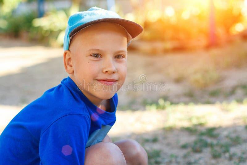 一个盖帽的一个男孩在自然微笑 E 免版税库存照片
