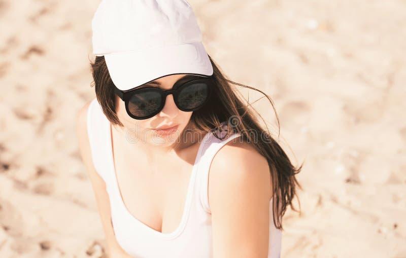 一个相当十几岁的女孩的画象有长发佩带的白色棒球帽、白色泳装和时髦太阳镜的 库存图片