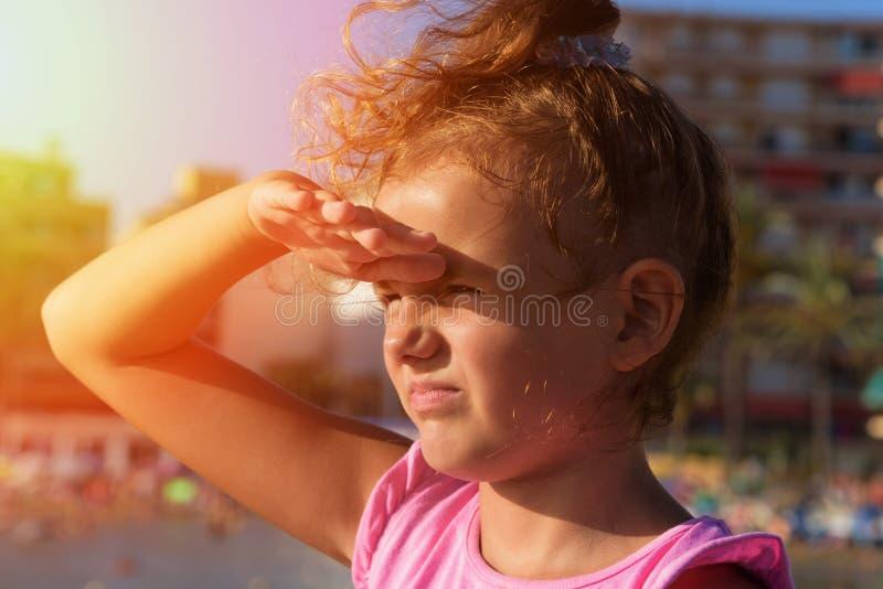 一个相当小女孩在阳光下从右到左很远看旁边,斜眼看和播放猿在城市海滩背景 S 库存图片