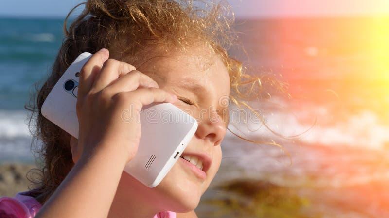 一个相当小女孩由智能手机讲话,微笑和斜眼看在海背景的阳光下 3日落 免版税图库摄影