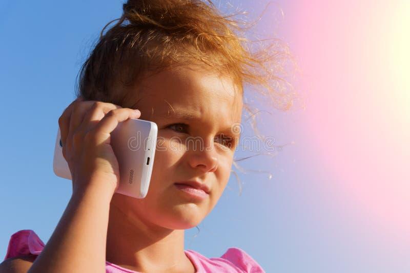 一个相当小女孩由智能手机讲话,斜眼看在蓝天背景的阳光下 3日落 免版税图库摄影