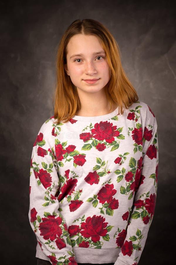 一个相当年轻微笑的红头发人女孩的画象 免版税库存图片