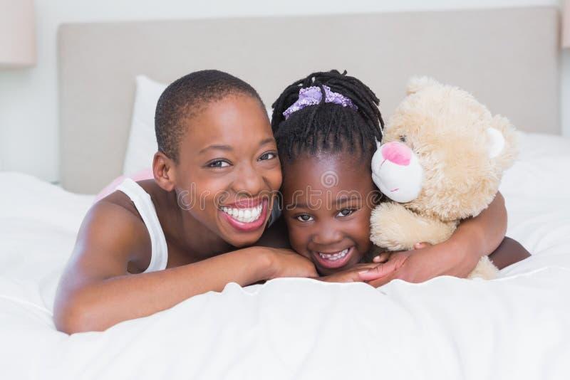 一个相当美丽的微笑的母亲的画象有她的女儿的在她的床上 免版税图库摄影