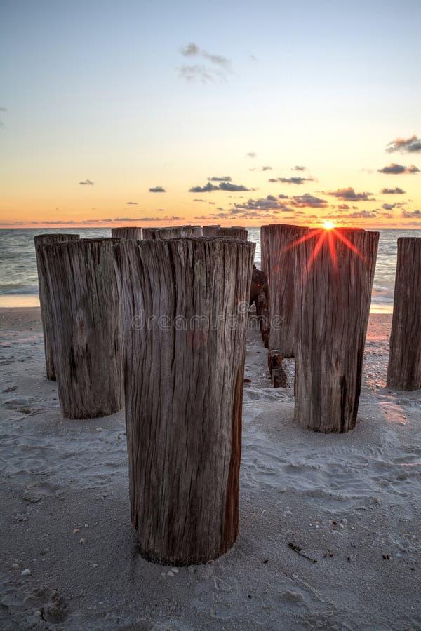 一个码头的被毁坏的废墟在口岸皇家海滩的在日落 库存图片