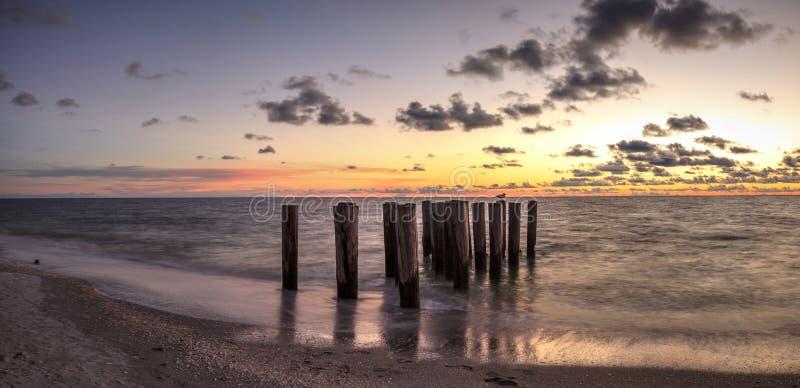 一个码头的被毁坏的废墟在口岸皇家海滩的在日落 免版税库存图片