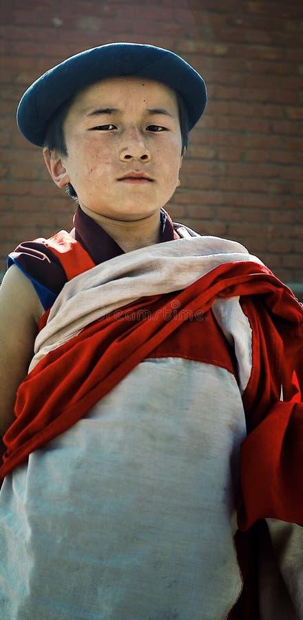 一个砖墙的fromt的年轻西藏佛教新手修士有一个传统礼服和帽子的 库存照片