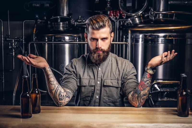 一个确信的被刺字的行家在衬衣的男性和头发的画象与时髦的胡子的在制片者啤酒厂 图库摄影