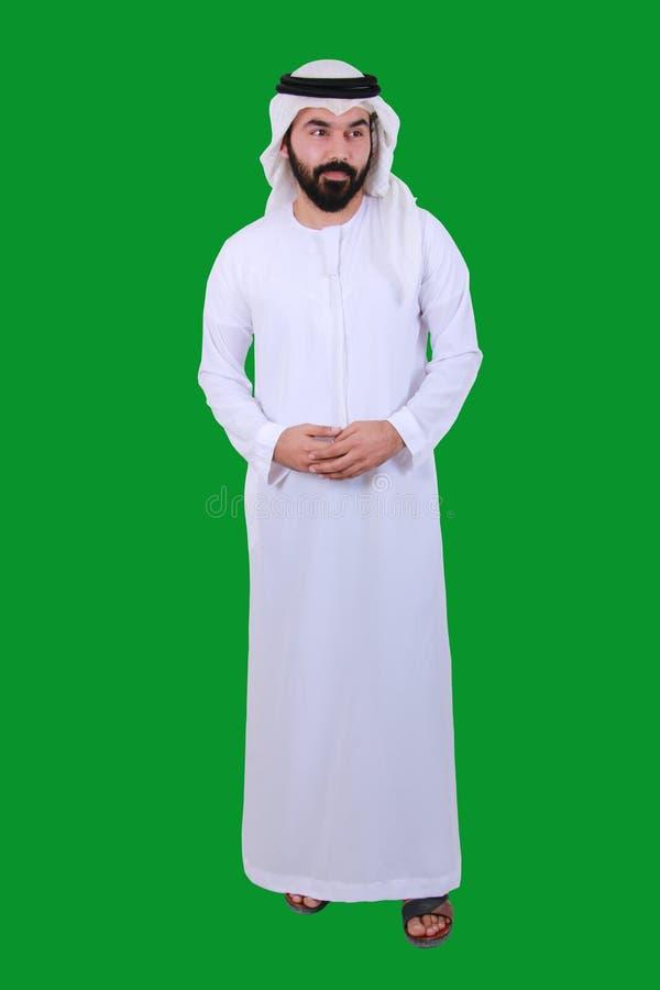 一个确信的阿拉伯中东人站立的和欢迎的微笑的和佩带的阿拉伯联合酋长国Emirati传统礼服 免版税库存图片