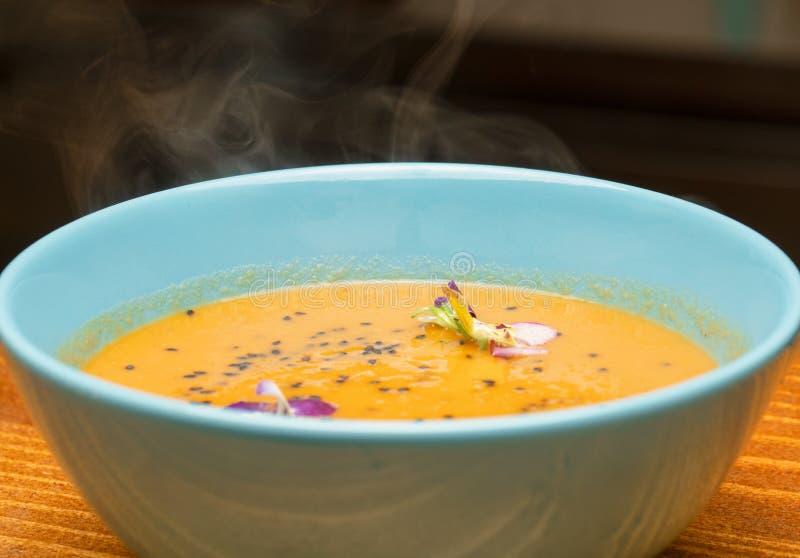 一个碗用在一个浅兰的碗的通入蒸汽的热的南瓜汤装饰与新鲜的蝴蝶花花和黑芝麻籽 秋天foo 库存照片