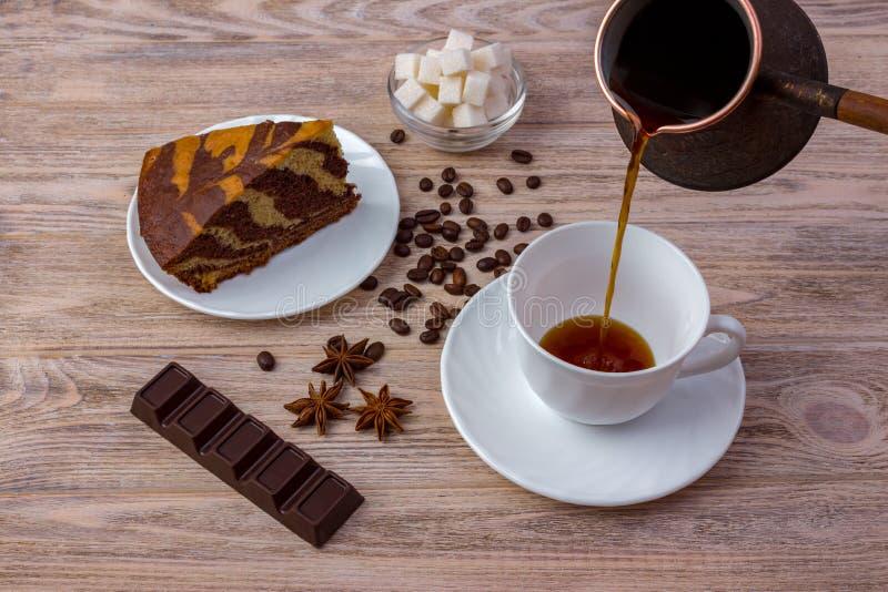 一个碗的顶视图有糖立方体、咖啡豆、惊人的蛋糕片断在茶碟和一杯咖啡的、茴香和巧克力ba 库存照片