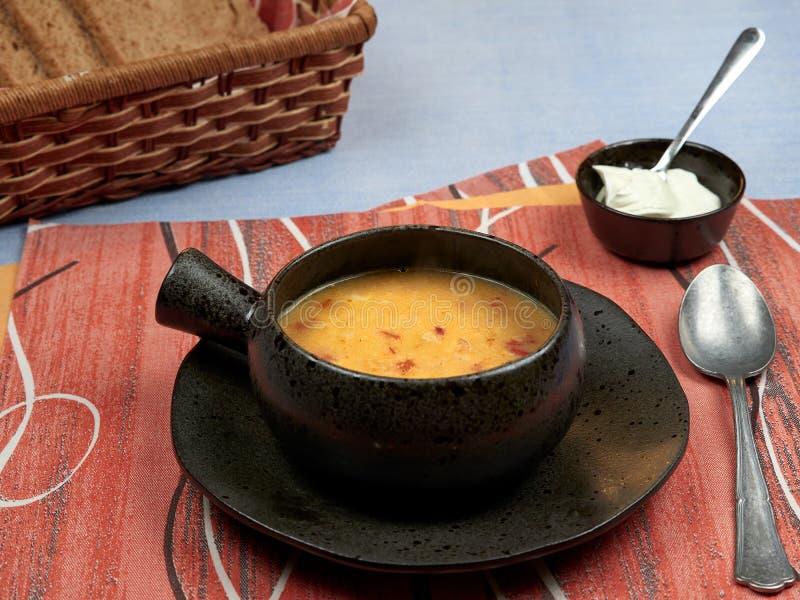 一个碗肚汤罗马尼亚语:在一张蓝色桌布安置的一块红色餐巾的Ciorba de Burta集合,服务与额外奶油和ba 免版税库存图片