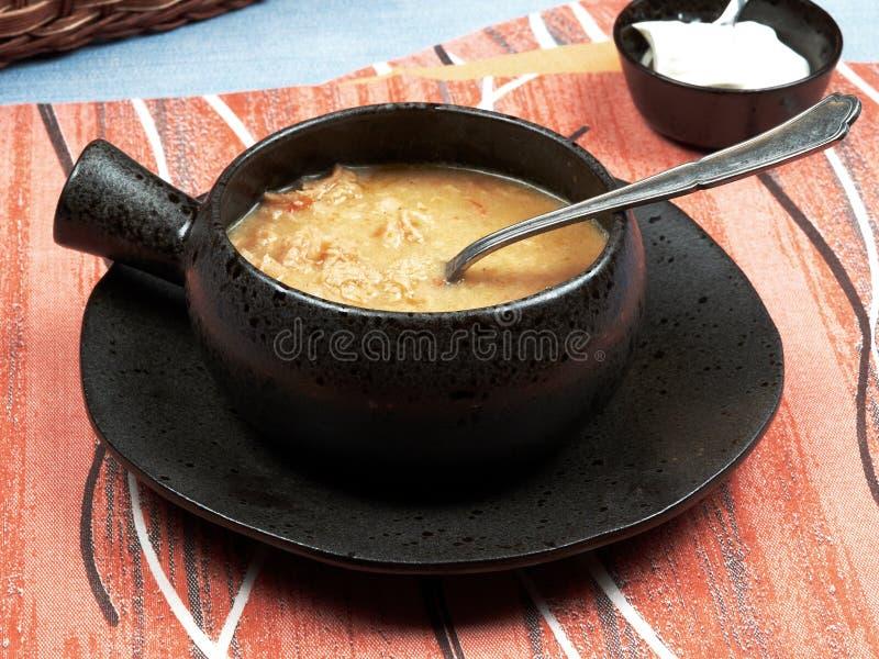 一个碗肚汤罗马尼亚语:在一张蓝色桌布安置的一块红色餐巾的Ciorba de Burta集合,服务与额外奶油和ba 免版税图库摄影