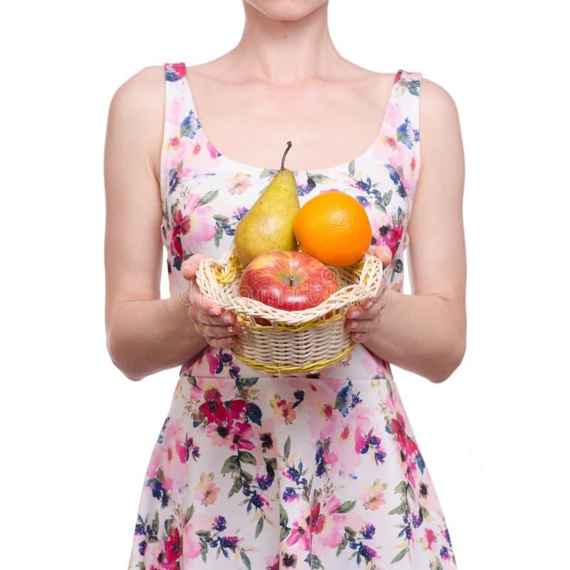 一个礼服花卉图案的妇女在荆条筐果子苹果梨桔子 库存图片